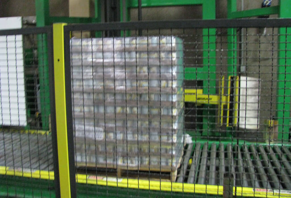 A machine shrink-wraps pallets of canned vegetables.